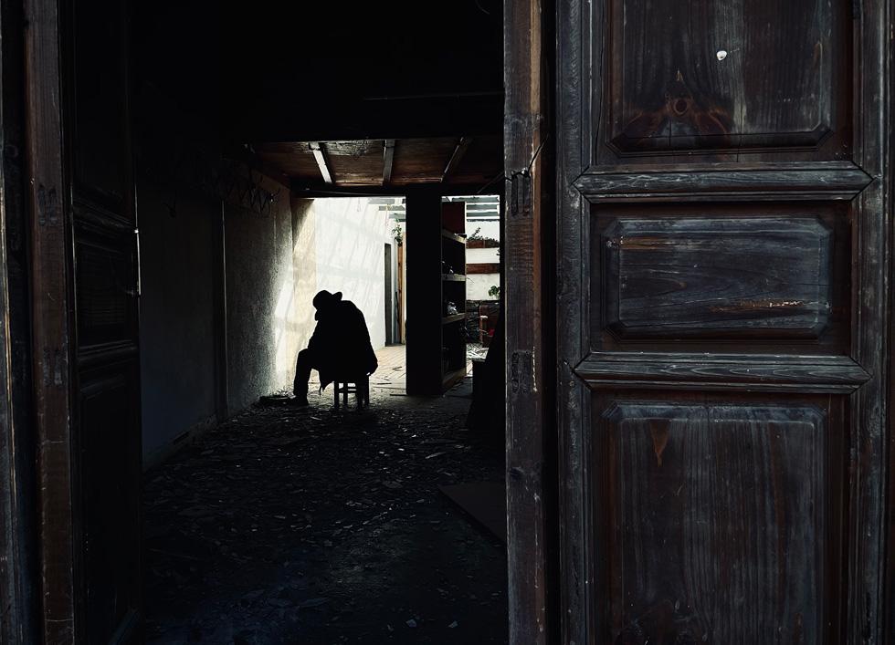 在敞开的门外,一个人影坐在碎片和阴影之中。