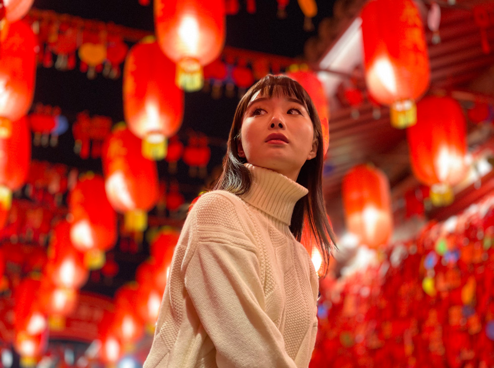 在发光的红色纸灯笼中拍摄的一名妇女串在头顶上。