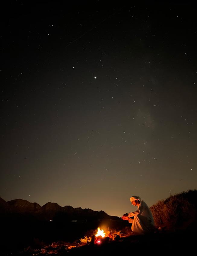 夜间射击了在篝火前面的一个人坐在沙漠。