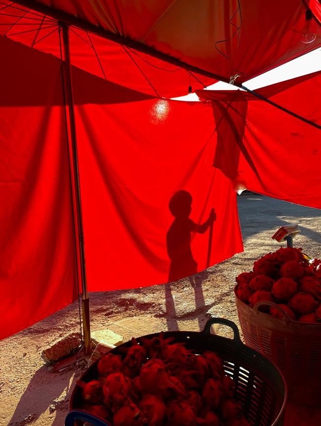 任务是遮住阳光的红色篷布引来孩子玩耍的阴影。