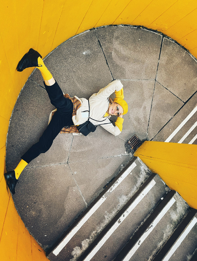 一个人在黄色墙间楼梯间的平台上摆姿势。